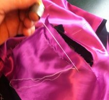 This picture shows me hand basting and fixing the lining into the inner coat armhole.